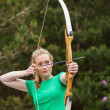 Stock Photo: Concentrating blonde wompracticing archery