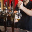 Stock Photo: Barkeeper pulling pint of beer