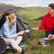 Happy couple cooking outdoors on camping trip — Photo