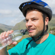 Fit man wearing helmet drinking water — Stock Photo