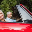 Side view of mature couple driving red convertible — Stock Photo