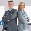 Two happy businesspeople looking at camera standing back to back — Stock Photo