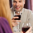 Happy man having glass of wine with his gorgeous girlfriend — Stock Photo