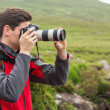 Handsome man on a hike taking a photograph — Stock Photo