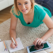 Stock Photo: Cheerful young woman lying on floor using tablet to do her assignment