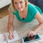 wesoły młoda kobieta, leżąc na podłodze przy użyciu tabletu do jej przypisania — Zdjęcie stockowe