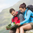Stock Photo: Couple resting after hiking uphill and reading map