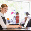 Attractive businesswoman working on laptop smiling at camera — Stock Photo