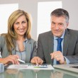 Two pleased business people smiling at camera analysing a graphic — Stock Photo