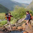 Foto Stock: Couple crossing river on hike