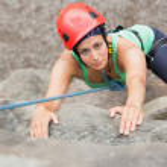 Determined girl climbing rock face — Stock Photo