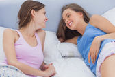 Happy friends resting in bed and talking — Stock Photo