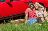 Smiling couple sitting on the grass having picnic together — Stock Photo