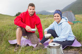 Couple cooking outside on camping trip smiling at camera — Stock Photo