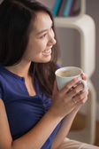 Happy asian woman sitting on the couch holding mug of coffee looking away — Stock Photo