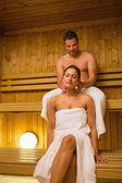 Man giving his girlfriend a neck massage in sauna — Stock Photo