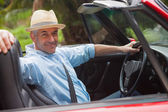 Smiling handsome man posing in red convertible — Stock Photo