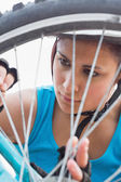 Athletic woman adjusting her spokes on bike wheel — Stock Photo