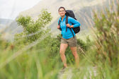 Female hiker with backpack walking and smiling — Stock Photo