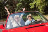 Mature couple in red cabriolet cheering at camera — Stock Photo