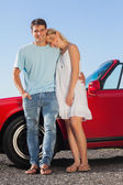 Happy cute couple posing against their red cabriolet — Stock Photo
