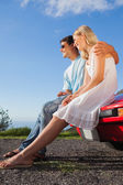 Cheerful couple sitting on their cabriolet car hood — Stock Photo