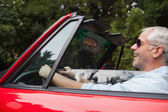 Smiling handsome man driving red convertible — Stock Photo