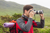 Sporty man on a hike taking a photograph — Stock Photo