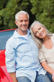 Cheerful mature couple sitting on their red convertible — Stock Photo