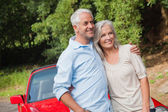 Happy mature couple posing by their red convertible — Stock Photo