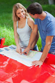 Smiling young couple reading map on their cabriolet bonnet — Stock Photo
