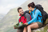 Couple resting after hiking uphill and holding map — Stock fotografie
