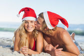 Man giving kiss to partner wearing christmas hats — Stock Photo