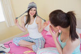 Funny girl trying on a wool hat for her laughing friend — Stock Photo