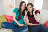 Smiling girl listening to music with her friend beside her on the sofa — Stock Photo