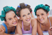 Friends in hair rollers and pajamas lying in bed — Stock Photo