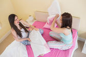Amigos felices en pijama con una almohada luchan en cama — Foto de Stock
