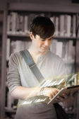 Concentrated student analysing graphs on his digital tablet — Stock Photo