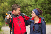Smiling couple going on a hike together looking at each other — Foto Stock
