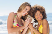 Two girls in bikinis listening to conch shell — Stock Photo