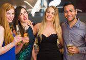 Portrait of smiling friends drinking beers — Stock Photo