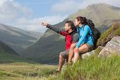 Coppia prendendo una pausa dopo trekking in salita con uomo che punta — Foto Stock