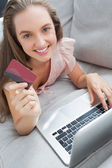 Woman shopping online with her laptop smiling at camera — Stock Photo