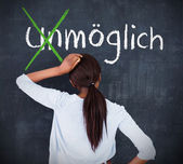 Attractive woman looking at a chalkboard with success in german on it — Stock Photo