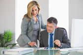 Attentive businesswoman explaining figures to a businessman — Stock Photo