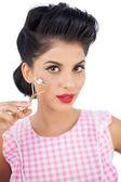 Gorgeous black hair model holding an eyelash curler — Stock Photo