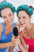Happy girls in hair rollers holding hairbrush — Stok fotoğraf