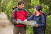 Smiling couple going on a hike together looking at map — Stock Photo