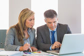 Attentive businessman showing something on computer to an attentive businesswoman — Stock Photo