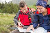 Casal usando o mapa e a bússola para encontrar o caminho — Foto Stock